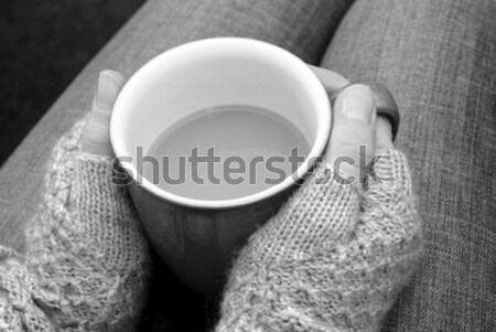 A woman in a cosy jumper holds a cup of tea or coffee on her lap Stock photo © sarahdoow