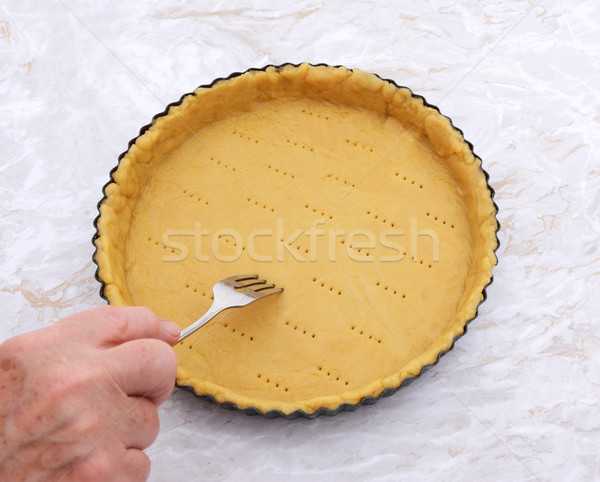 Woman finishes pricking holes in a pastry pie crust Stock photo © sarahdoow