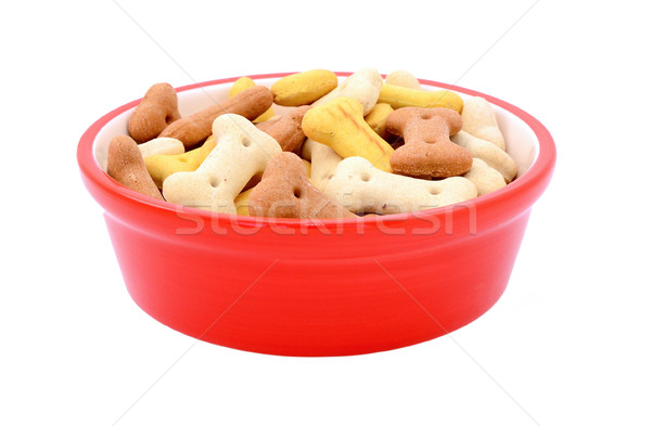 Dry bone-shaped dog biscuits in a red pet food bowl Stock photo © sarahdoow