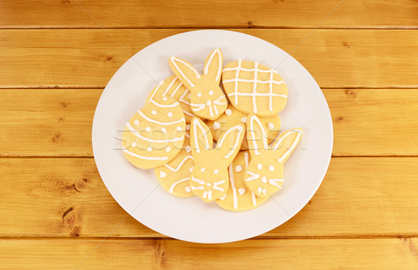 Plate full of frosted Easter cookies on a wooden table Stock photo © sarahdoow