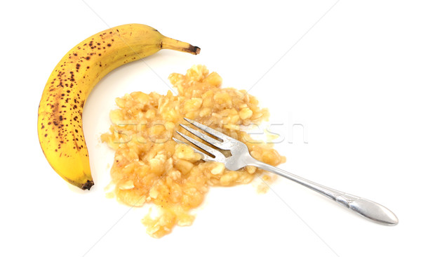 Overripe unpeeled banana with fork and pureed fruit Stock photo © sarahdoow
