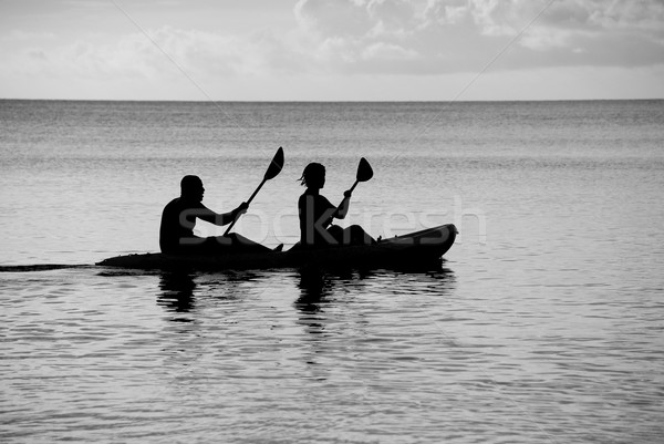 Kayakers silhouetted on the ocean Stock photo © sarahdoow