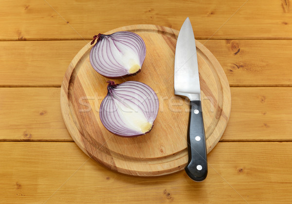 Red onion cut in half with a knife on a cutting board Stock photo © sarahdoow