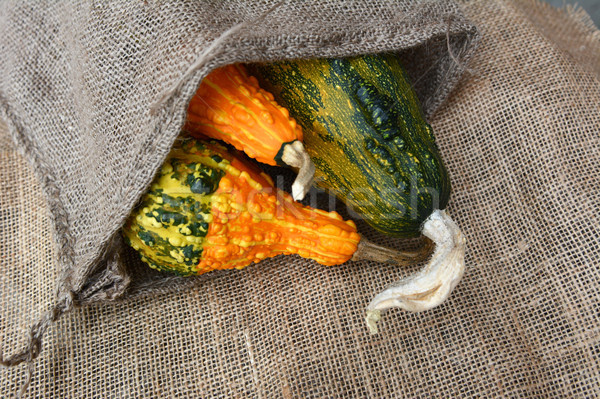 Three green and orange warty ornamental gourds in hessian sack  Stock photo © sarahdoow