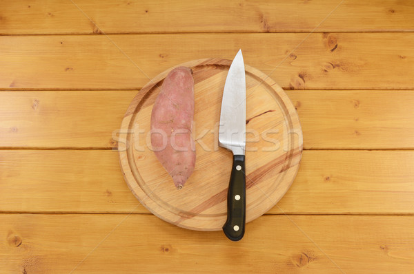 Sweet potato with a knife on a chopping board Stock photo © sarahdoow