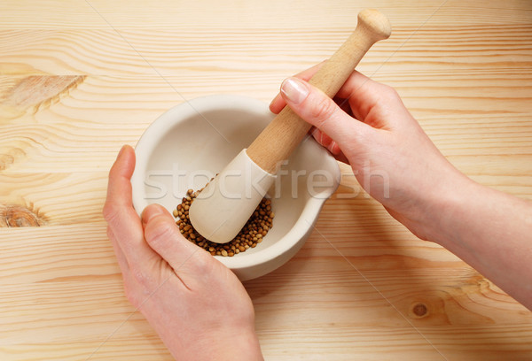 Two hands holding a pestle and mortar with whole coriander seeds Stock photo © sarahdoow