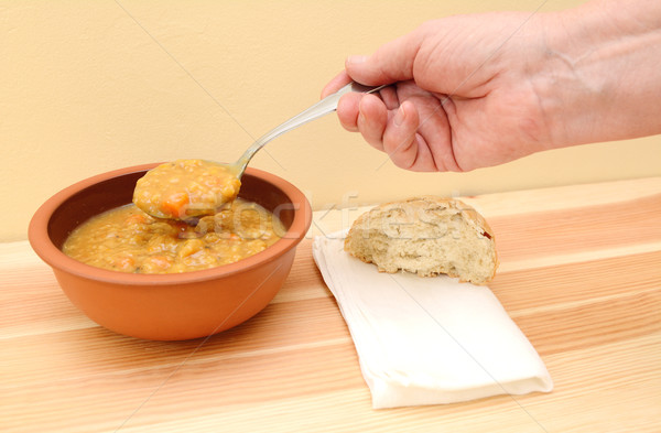 Hand holds spoonful of soup with bread roll and napkin on table Stock photo © sarahdoow