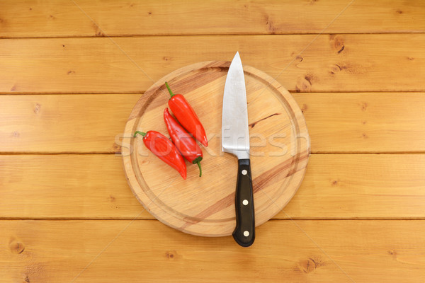 Three red peppers with a knife on a chopping board  Stock photo © sarahdoow