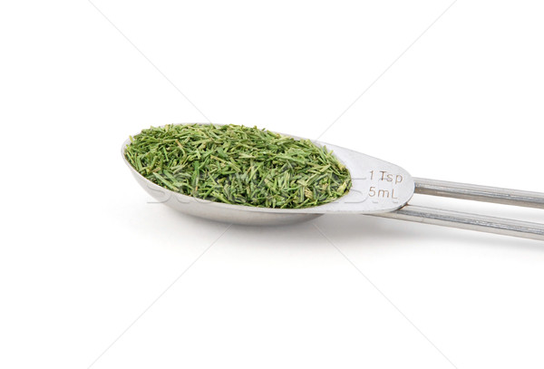 Stock photo: Dill tops measured in a metal teaspoon