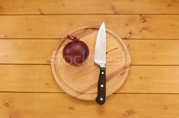Red onion with a knife on a chopping board Stock photo © sarahdoow