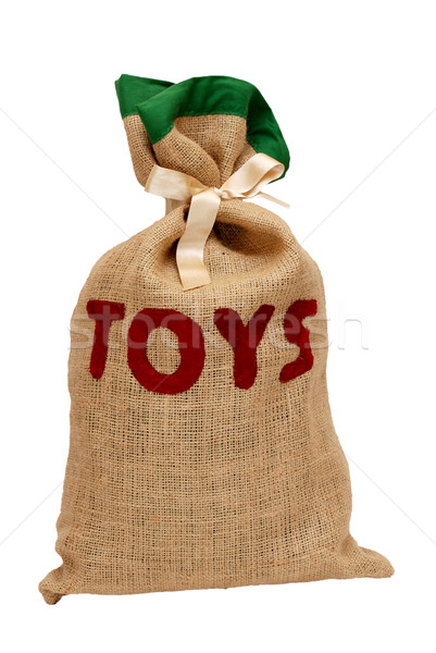 Stock photo: Santa's hessian sack full of toys and tied with satin ribbon