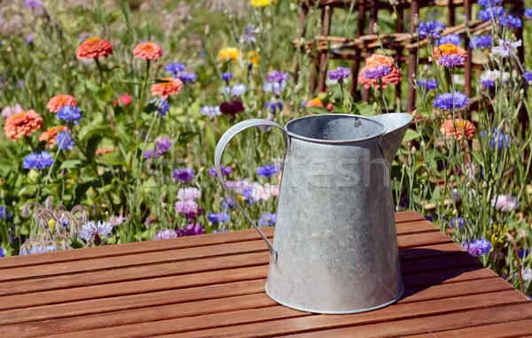 Empty metal pitcher on a table in a flower garden Stock photo © sarahdoow
