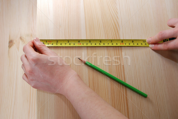 Two hands measure a wooden board with a steel tape measure Stock photo © sarahdoow
