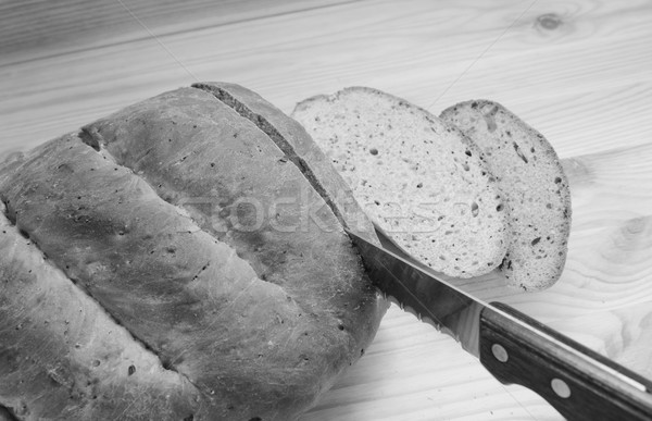 Cutting slices of bread on a wooden table Stock photo © sarahdoow