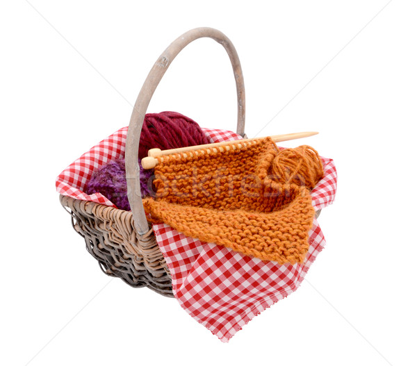 Stock photo: Purple, red and orange wool with knitting in a basket