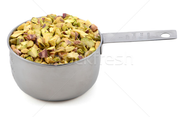 Chopped pistachio nuts in a metal cup measure Stock photo © sarahdoow