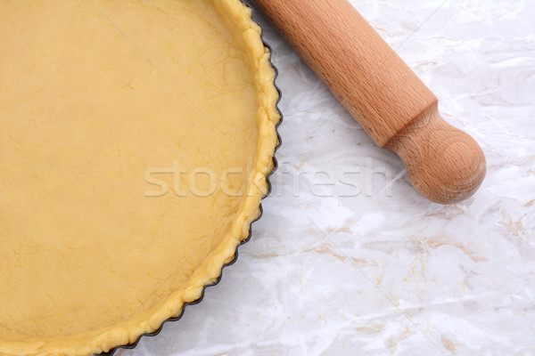 Baking tin lined with pastry, wooden rolling pin beside Stock photo © sarahdoow