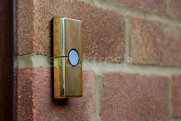 Sonnette mur de briques or laiton maison Photo stock © sarahdoow