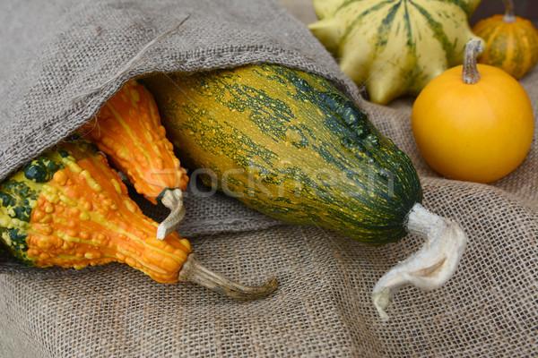 Assortment of orange and green ornamental gourds on rough hessia Stock photo © sarahdoow