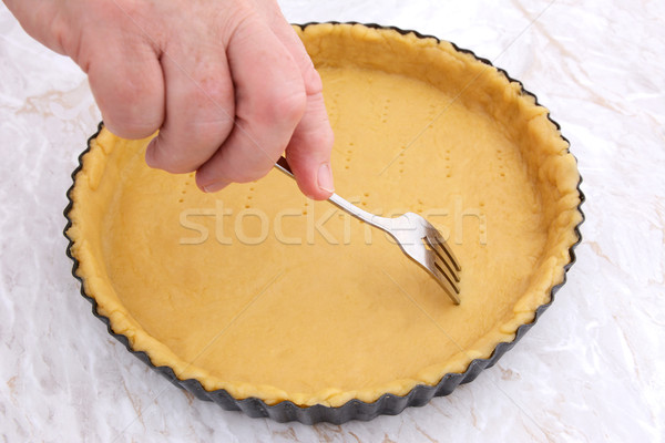 Woman using fork to prick holes in an uncooked pie crust Stock photo © sarahdoow