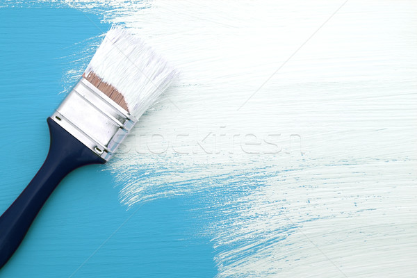 Paintbrush with white paint painting over blue Stock photo © sarahdoow