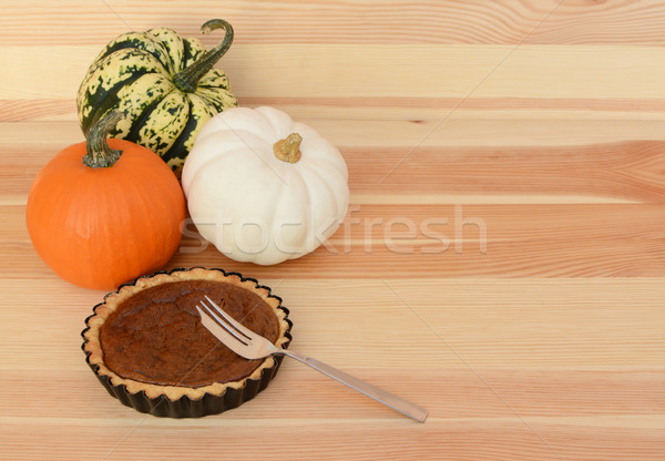 Three pumpkins with small pumpkin pie and fork Stock photo © sarahdoow