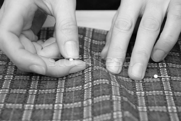 Closeup of two hands pinning plaid fabric Stock photo © sarahdoow