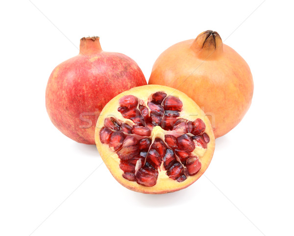 Stock photo: Two pomegranates and a cut half showing seeds