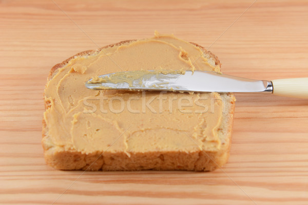 Smooth peanut butter being spread onto bread Stock photo © sarahdoow