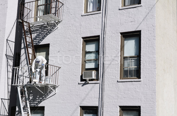 Painter dressed in coveralls, painting metal fire escape white  Stock photo © sarahdoow