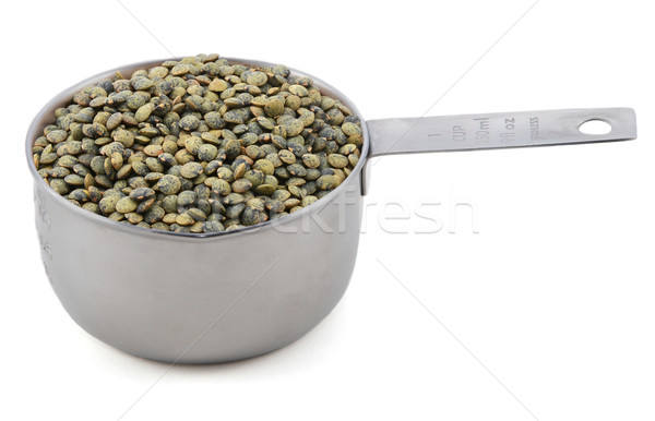 Stock photo: Marbled dark green lentils in a cup measure