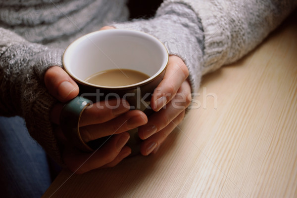 Woman holds hot drink at a table under lamplight Stock photo © sarahdoow
