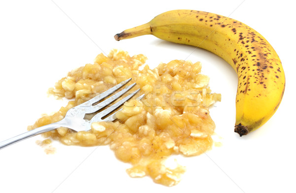 Closeup of mashed banana with fork and an unpeeled fruit Stock photo © sarahdoow