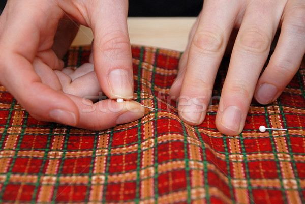 Closeup of two hands pinning red plaid fabric Stock photo © sarahdoow