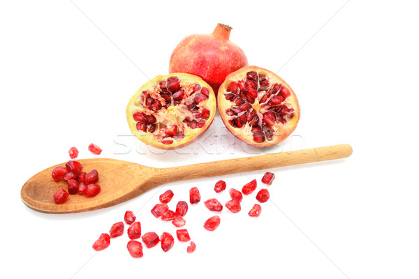 Pomegranate and two cut halves with seeds removed with spoon Stock photo © sarahdoow