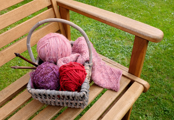 Stock photo: Basket of knitting and yarns on a bench