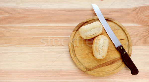 Two bread rolls, a knife and wooden cutting board Stock photo © sarahdoow
