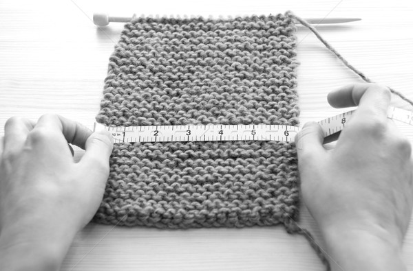 Two hands measuring knitting in inches Stock photo © sarahdoow