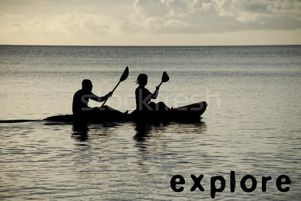 Kayakers silhouetted on the ocean, EXPLORE as concept text Stock photo © sarahdoow