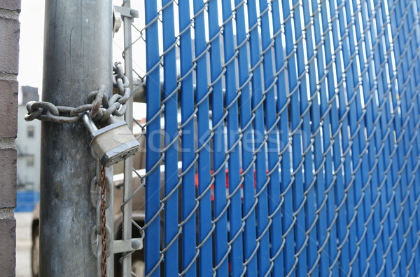 Heavy-duty padlock and chain on blue security gate Stock photo © sarahdoow
