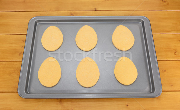 Six egg shaped Easter biscuits on a baking tray  Stock photo © sarahdoow
