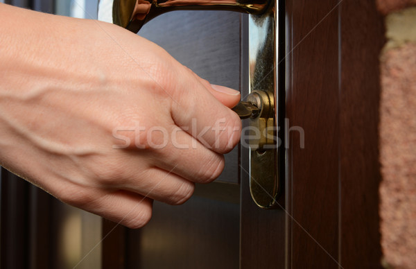 Woman turns the key in a lock on an external door Stock photo © sarahdoow