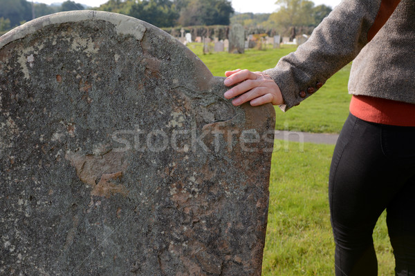 Woman's hand resting on a gravestone Stock photo © sarahdoow