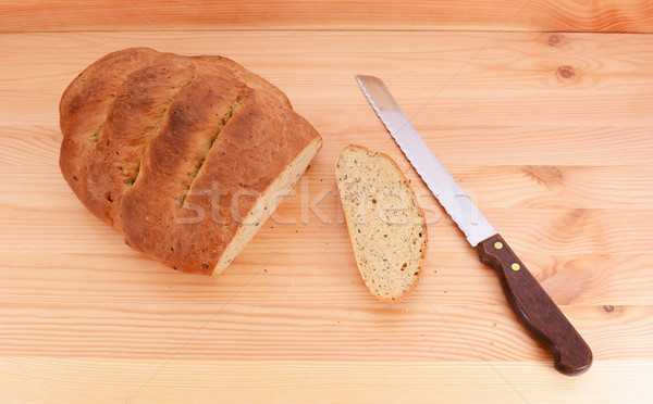Stock photo: Bread knife with a freshly baked loaf