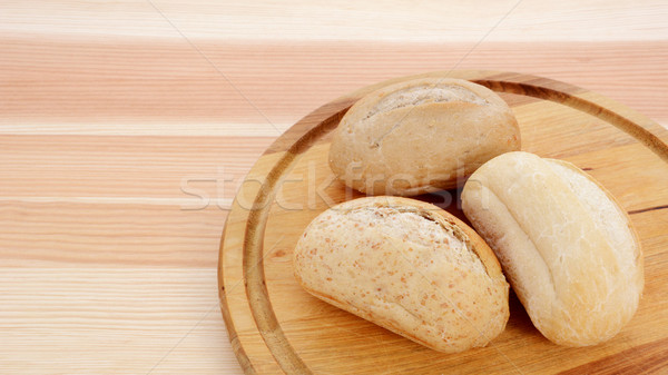 Stock photo: Three crusty petit pain on a bread board
