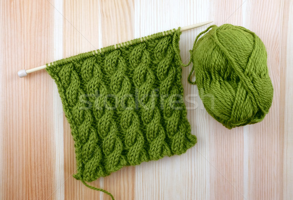Stock photo: Green cable stitch knitting with a ball of yarn
