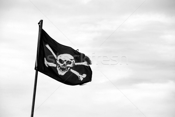 Torn Jolly Roger flies from flagpole Stock photo © sarahdoow