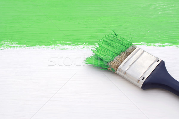 Paintbrush with green paint, painting over white board Stock photo © sarahdoow