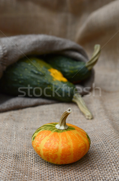 Disc-shaped ornamental gourd and large green gourds on hessian Stock photo © sarahdoow