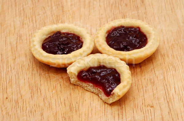 Three jam tarts, one with a bite taken, on a wooden table Stock photo © sarahdoow